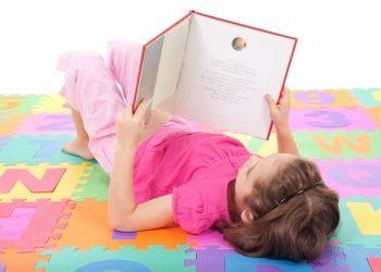 dreamstime_m_18754776 little girl reading on matt